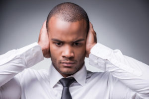 Hear no evil. Young African man in shirt and tie covering ears with hand while standing against grey background
